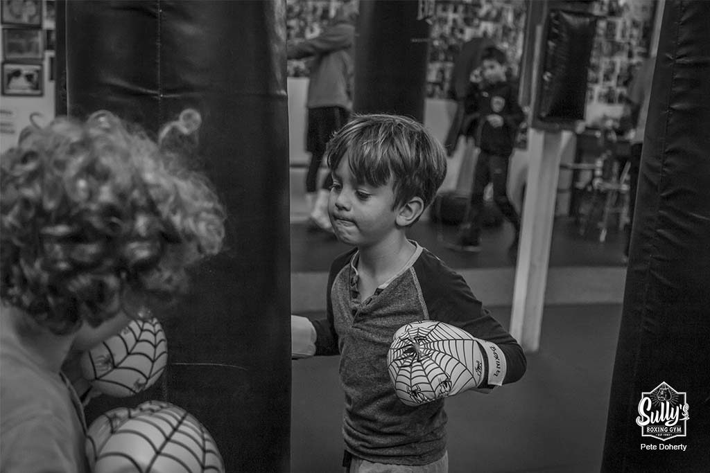 children hitting heavy bags at sullys boxing gym toronto