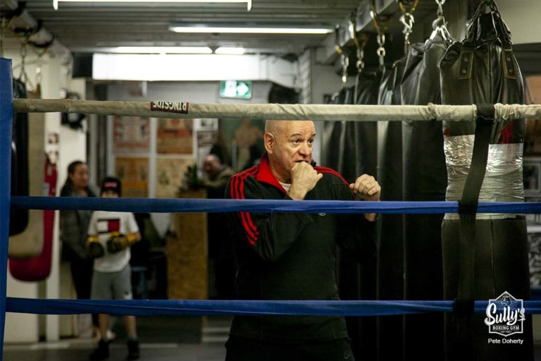 coach rico mancini instructing a teen boxer